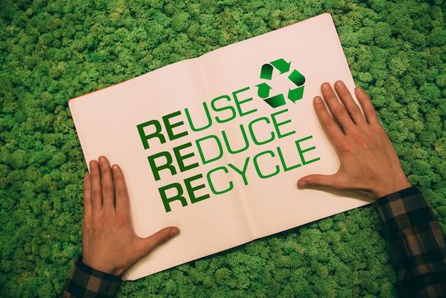 Verde vivo. immagine ravvicinata vista dall'alto dell'uomo che si tiene per mano sul suo taccuino con testo e simbolo di riciclo su sfondo di muschio