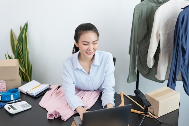 Concetto di shopping dal vivo un commerciante femminile che risponde ai messaggi dei clienti che spiegano informazioni e promozioni delle merci.