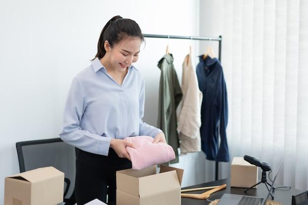 Concetto di shopping dal vivo un commerciante femminile che imballa i prodotti in scatole dopo aver ricevuto ordini dai clienti.