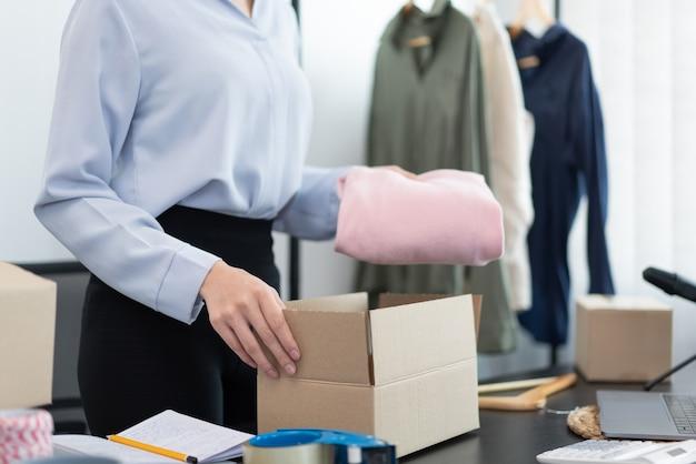 Concetto di shopping dal vivo un commerciante femminile che imballa prodotti in scatole