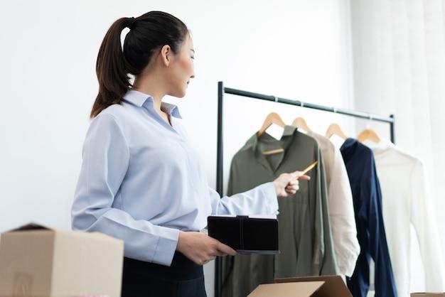 Concetto di shopping dal vivo una venditrice che trasmette un livestream che vende magliette a maniche lunghe funzionanti sui social media.