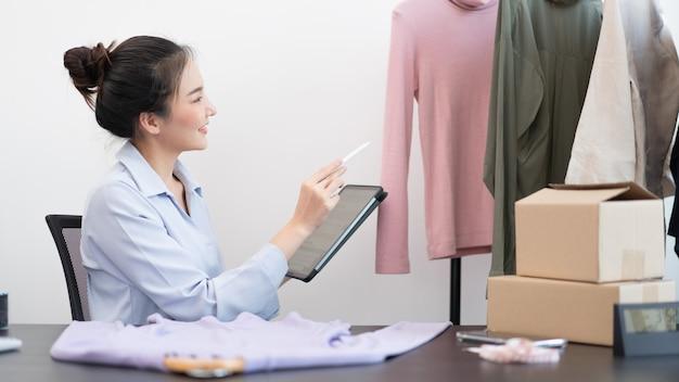 Concetto di shopping dal vivo un venditore femminile che conta uno stock e controlla un numero di pacchi prima di inviarlo ai clienti tramite consegna postale.