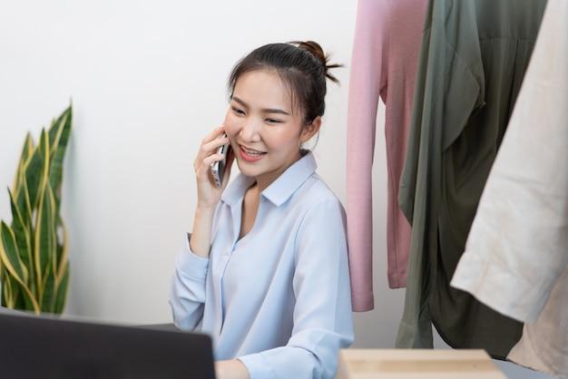 Concetto di shopping dal vivo una venditrice che parla al telefono cellulare con il suo partner commerciale della vendita e delle scorte di merci.