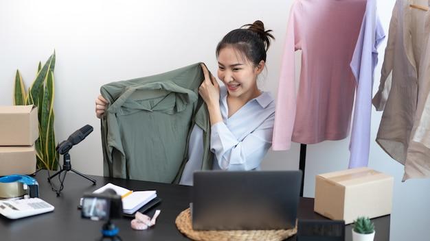 Concetto di shopping dal vivo una venditrice che parla con i clienti online che mostrano un prodotto