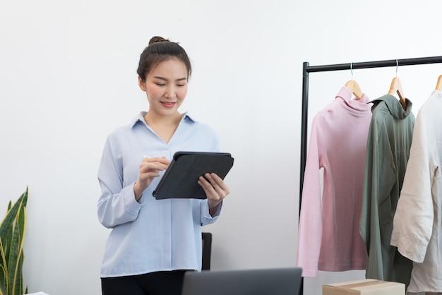 Concetto di shopping dal vivo un commerciante femminile che carica informazioni e foto della merce sul suo negozio online.