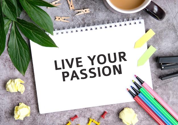 Vivi la tua passione su un quaderno con una tazza di caffè, fogli compressi, pastelli e pinzatrice
