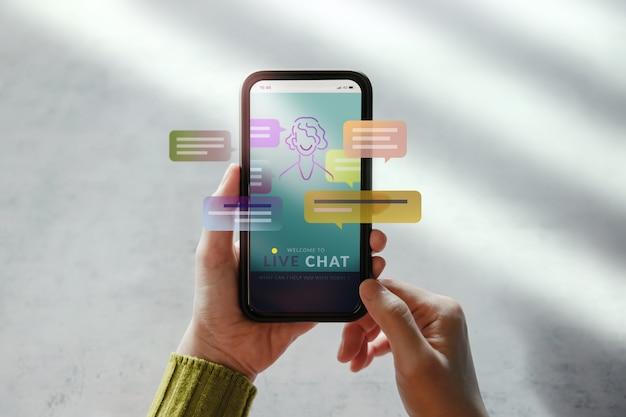 Concetto di tecnologia livechat. cliente che utilizza il telefono cellulare per conversare con un'intelligenza artificiale. assistente virtuale per informazioni sull'assistenza clienti
