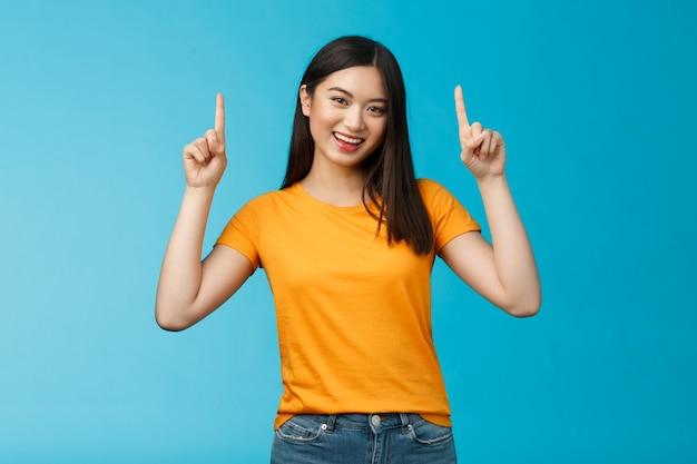 Vivace ragazza asiatica taglio di capelli corto scuro, inclinare la testa con un sorriso carino, alzare le mani e puntare l'indice verso l'alto, introdurre la promozione superiore, sorridere, vantarsi di un nuovo acquisto interessante, stare in piedi sullo sfondo blu.