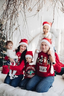 Genitori vivaci con bambini carini in abiti abbinati sorridenti e inginocchiati vicino all'albero di natale