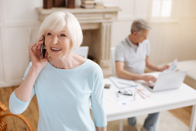 Vivace donna invecchiata sincera che parla con qualcuno al telefono mentre utilizza il suo smartphone per comunicare con i colleghi