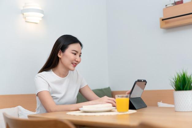 Concetto di soggiorno una ragazza con i capelli lunghi seduta in soggiorno che naviga in internet con il suo smartphone.