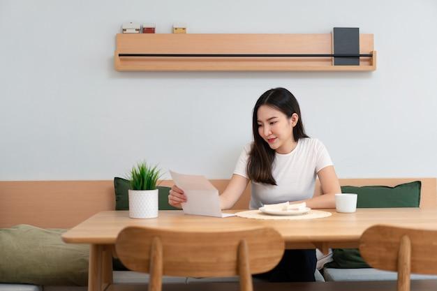 Concetto di soggiorno una bella signora in possesso di un foglio da leggere mentre un'altra mano tiene una tazza di bevanda alla caffeina nel soggiorno.