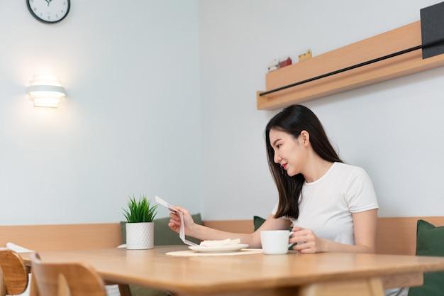 Concetto di soggiorno una bella signora in possesso di un foglio da leggere mentre un'altra mano tiene una tazza di bevanda alla caffeina nel soggiorno. Foto Premium