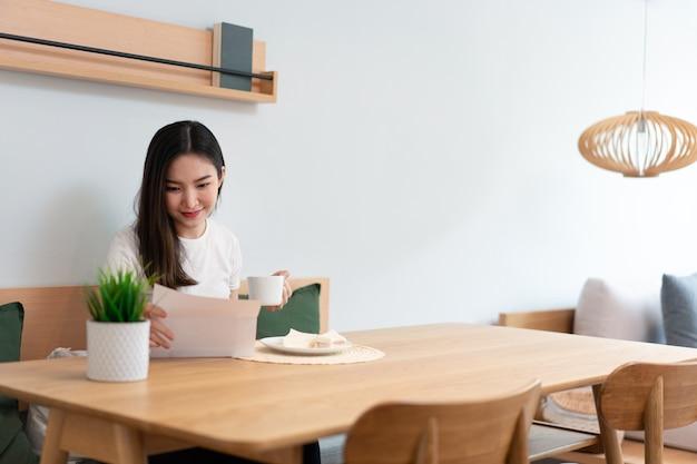 Concetto di soggiorno una bella signora che tiene un foglio da leggere mentre un'altra mano tiene una tazza di bevanda alla caffeina nel soggiorno.
