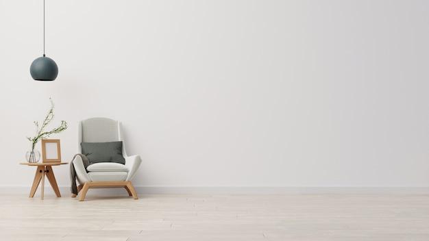 Soggiorno parete interna con poltrona di velluto grigio chiaro, cuscino grigio, plaid, tavolino e ramo di pianta verde in vaso su sfondo bianco muro vuoto.