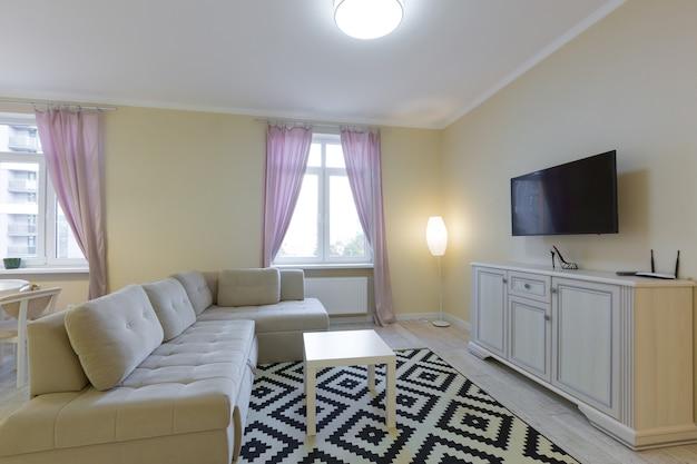 Interno soggiorno, con ampio divano e tv, con tende viola, stile moderno in colori chiari