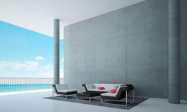 Il soggiorno e la decorazione dei mobili simulati e lo sfondo del muro di cemento e la vista sul mare
