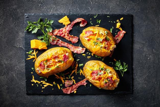Patate appena sfornate caricate con pancetta, petto di pollo tirato e cheddar su una lastra di ardesia nera su un tavolo di cemento, vista orizzontale dall'alto, close-up, flatlay