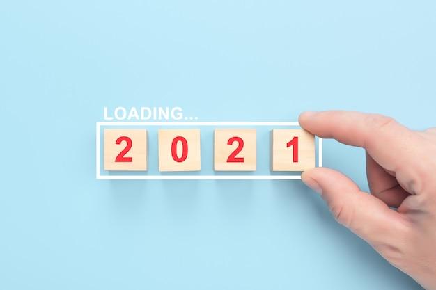 Caricamento 2021 anni su cubi di legno su sfondo blu. mano mettendo cubo di legno nella barra di avanzamento.