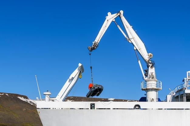 Caricamento gommone con conducente sul ponte utilizzando la gru della nave. spedizione artica.