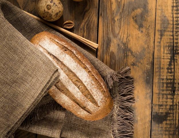 Una pagnotta di pane su un tovagliolo di stoffa su una superficie di legno, vista dall'alto