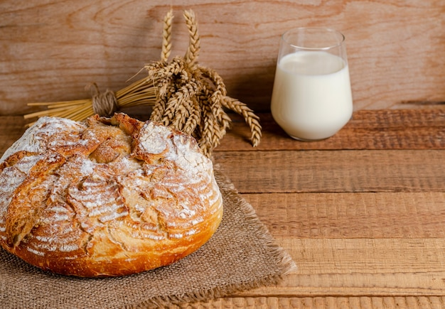 Una pagnotta di farina di frumento, un bicchiere di latte su assi di legno