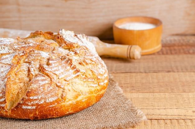 Pagnotta di pane a base di farina di frumento su assi di legno Foto Premium