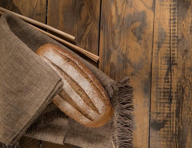 Una pagnotta di pane su un tovagliolo e spighette su una superficie di legno, vista dall'alto