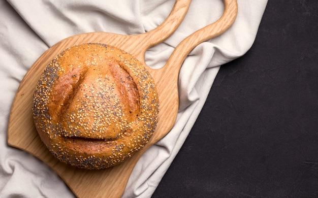 Pagnotta di pane con semi di sesamo e semi di papavero su un tessuto di lino bianco su uno spazio nero. copia spazio