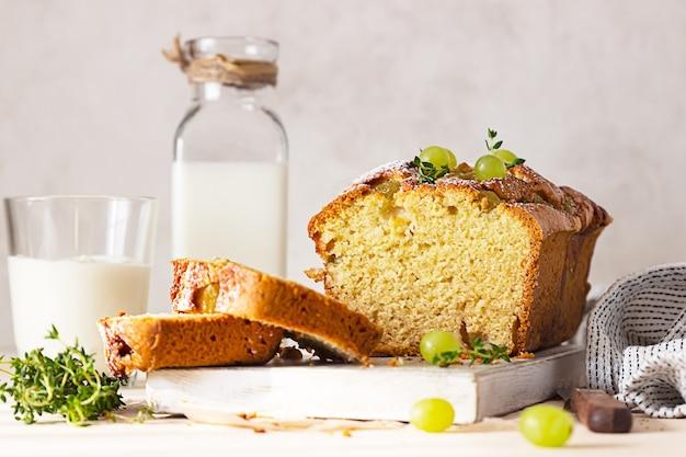 Torta di pagnotta con polenta, uva, timo e zucchero a velo su tavola di legno bianca.