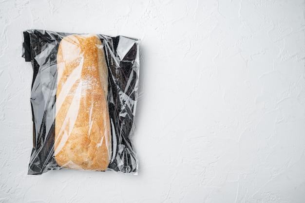 Pagnotta di pane ciabatta di grano intero artigianale appena sfornato in un sacchetto del mercato, su sfondo bianco, vista dall'alto laici piatta, con copyspace e spazio per il testo