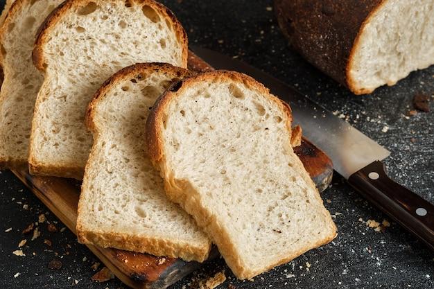 La pagnotta di pane bianco fresco affettato viene stesa su un tagliere, accanto a un coltello affilato