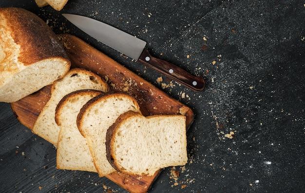 Pagnotta di pane bianco fresco affettato steso su un tagliere e un coltello affilato nelle vicinanze