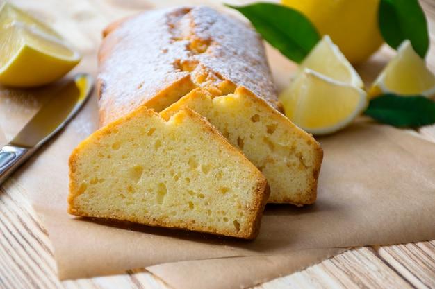 Pagnotta di torta senza glutine lemo con pezzi di limone, foglie verdi e coltello su fondo di legno rustico.