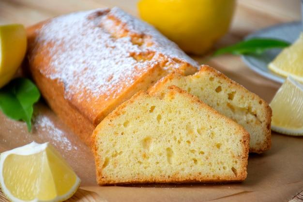 Pagnotta di torta al limone senza glutine con zucchero in polvere, pezzi di limone, foglie verdi su fondo di legno rustico.