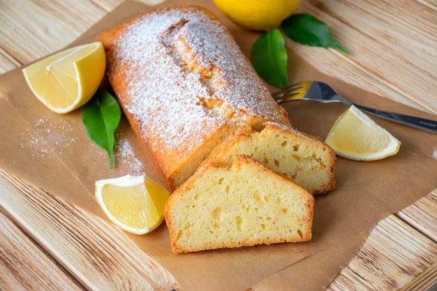 Pagnotta di torta al limone senza glutine con zucchero in polvere, pezzi di limone, foglie verdi