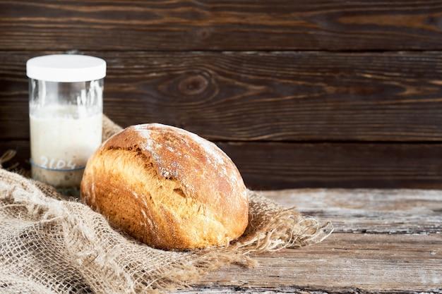 Pagnotta di pane a lievitazione naturale di latte bianco fatto in casa, fuoco selettivo. un bicchiere di lievito naturale sul tavolo. close-up, con copia spazio. pane artigianale su un rivestimento in tessuto, fondo in legno