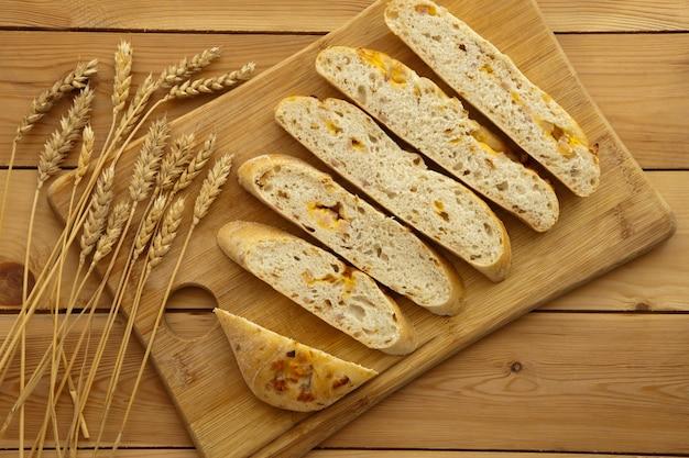 Pagnotta di pane biologico su fondo di legno con formaggio e prosciutto. pane fresco integrale. concetto di cibo naturale.