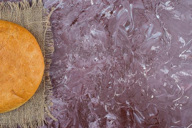 Una pagnotta di pane tondo con una crosta su una tela di sacco
