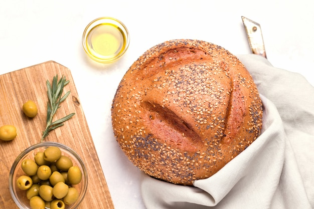 Una pagnotta di pane bianco rotondo su un piatto bianco accanto a olive e burro. pane fatto in casa