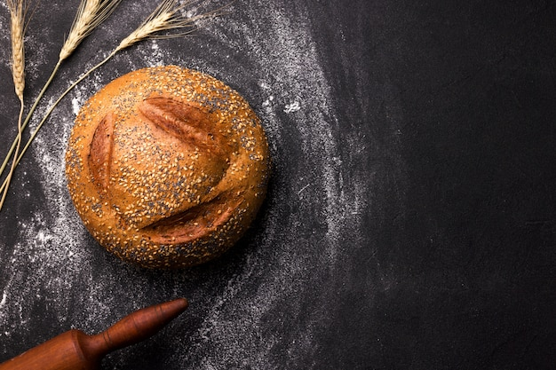 Pagnotta di pane bianco rotondo con semi di sesamo e semi di papavero su uno spazio nero. copia spazio