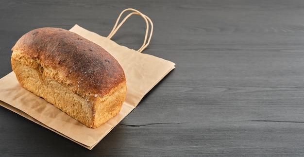 Il pane rustico della pagnotta sul sacchetto di carta sulla tavola di legno nera è preparato per la consegna all'acquirente. idea di piccola impresa, cottura e consegna di pane a lievitazione naturale sano su ordinazione. vista dall'alto con copia spazio