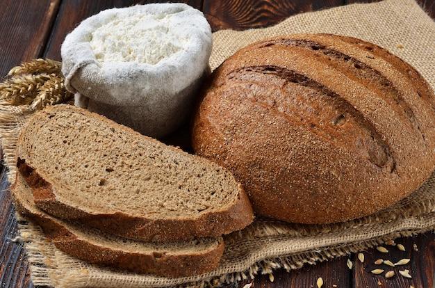 Una pagnotta di pane di crusca di segale con fette su sfondo vestirono
