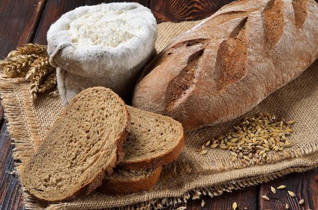 Pagnotta di pane di segale con fette su sfondo di tela di sacco