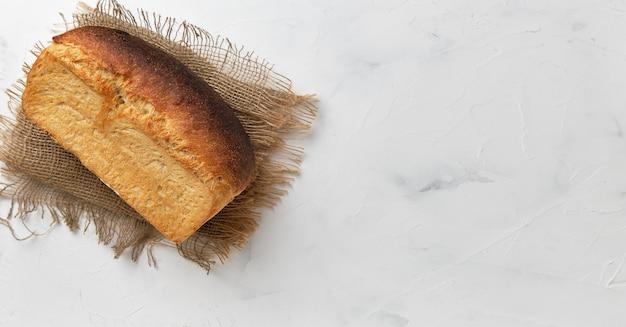 Una pagnotta di pane rustico bianco su una fodera di lino su un tavolo bianco