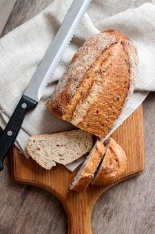 Pagnotta di pane integrale con fette sul bordo di legno sul tavolo della cucina