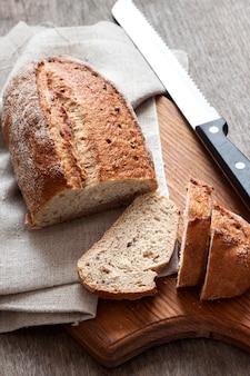 Pagnotta di pane integrale con le fette sul bordo di legno
