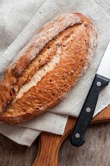 Pagnotta di pane di grano intero bordo di legno sul tavolo della cucina. vista piana laico e dall'alto