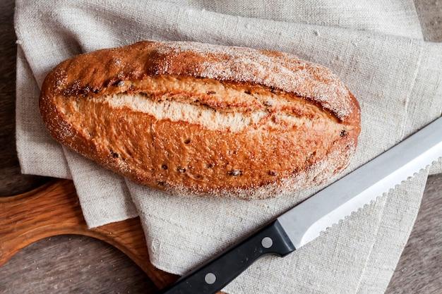 Pagnotta di pane integrale in legno bordo sul tavolo da cucina.
