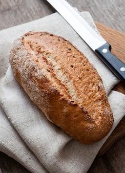 Pagnotta di pane di grano intero bordo di legno sul tavolo della cucina